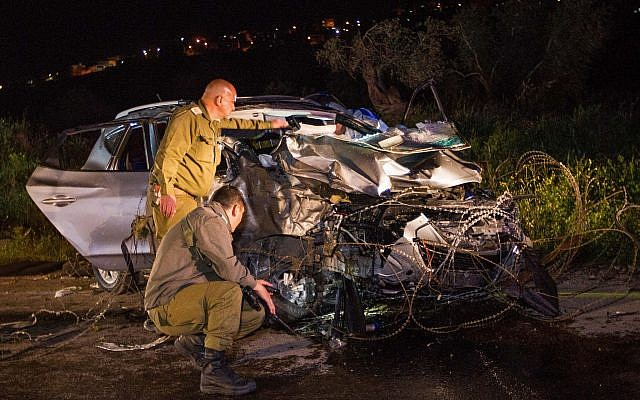 Israeli soldiers inspect a car at the scene where two Israeli soldiers were killed and another two were injured in a car-ramming terror attack near Mevo Dotan, in the West Bank, March 16, 2018. (Meir Vaknin/Flash90)