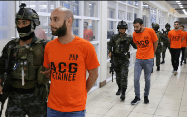 In this photo provided by the Philippine National Police, SAF (Special Action Force) members escort Israeli nationals following a raid at Clark Freeport Zone, Pampanga province, June 7, 2018, in Quezon city, northeast of Manila, Philippines. (Philippine National Police via AP)