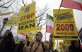 Supporters of Maryam Rajavi, President of the National Council of Resistance of Iran, demonstrate against Iranian President Hassan Rouhani's visit in Paris, Wednesday, Jan. 27, 2016. Banner on the right reads 'Human rights. No complaisance. 2000 executions after 2 years with Rohani.' (AP Photo/Christophe Ena)