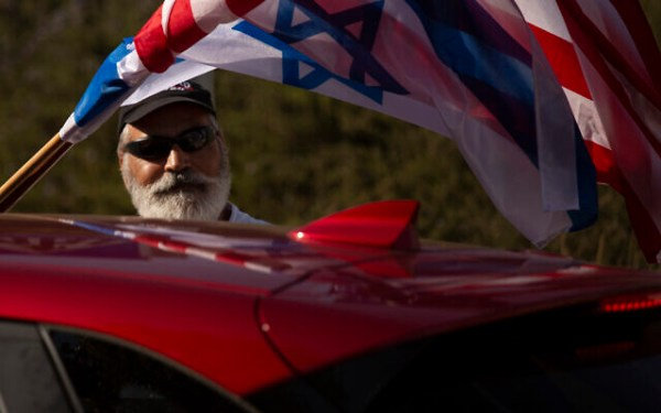 An Israeli supporter of the re-election of US President Donald Trump waves American and Israeli flags from a car at a rally outside of the US Embassy, in Jerusalem, Tuesday, Oct. 27, 2020. (AP Photo/Maya Alleruzzo)