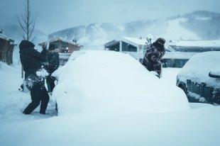 Sportliche Schneeballschlacht über Sportliches Auto weckt die Kinder in den Männern