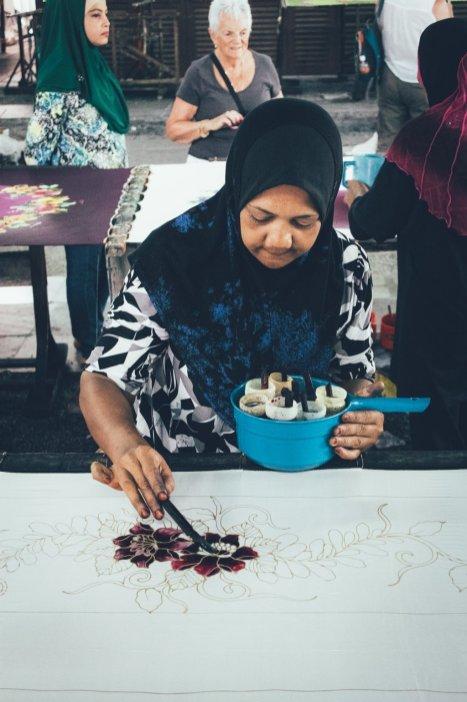 Craft Batik Artist, die die Wachsoutlines von Hand füllt