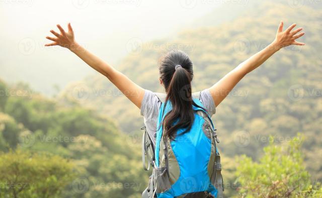 incoraggiante escursionismo donna a braccia aperte al picco di montagna 945357 Foto d'archivio