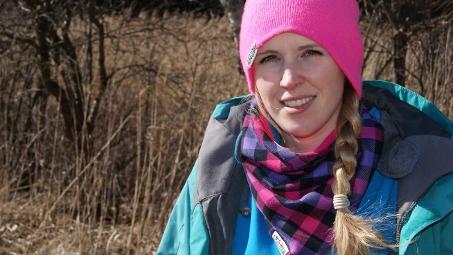 A picture of Cat Ekkelboom-White wearing a ski jacket and pink beanie in the woods