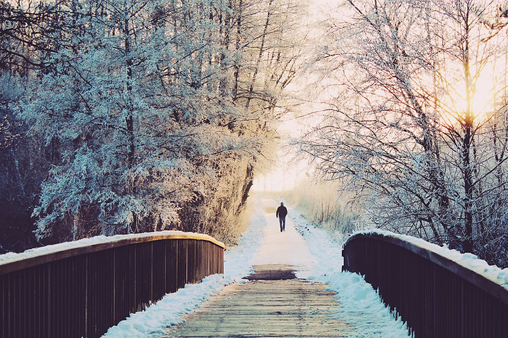 Man walking towards bridge during winter