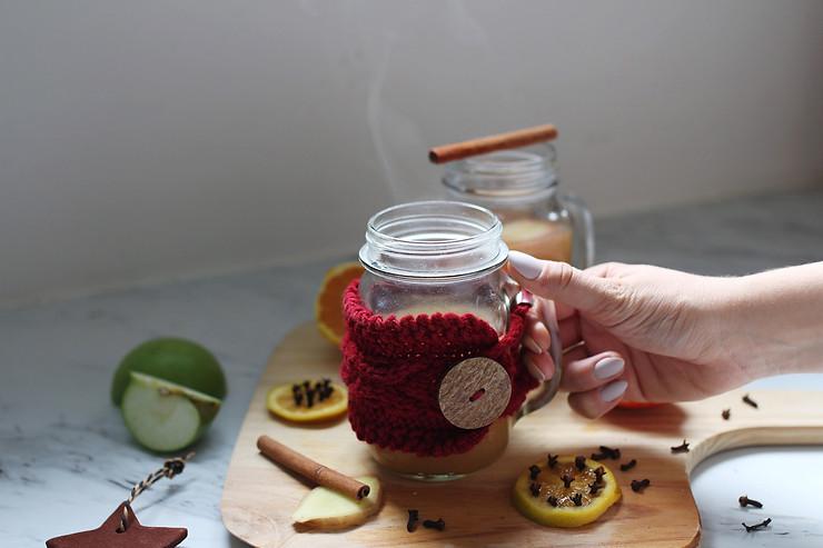 Warm apple cider in mason jar with drink cozy