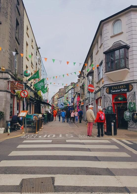 ciudad de Galway llegar a la ciudad road trip en irlanda cielo gris banderines de colores irlandeses turistas