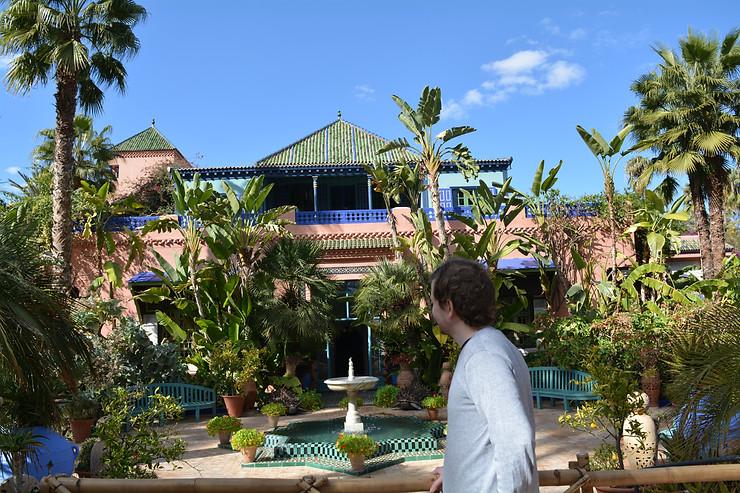 jardines de majorelle, marrakech, hombre mirando, turistas, palmeras, color verde, día soleado, ciudad roja
