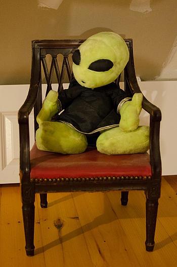 alien stuffie sitting in a chair earthling pannellbytes