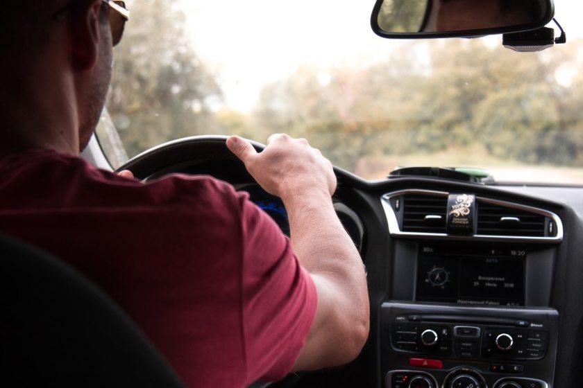foto tirada do banco traseiro de motorista dirigindo carro