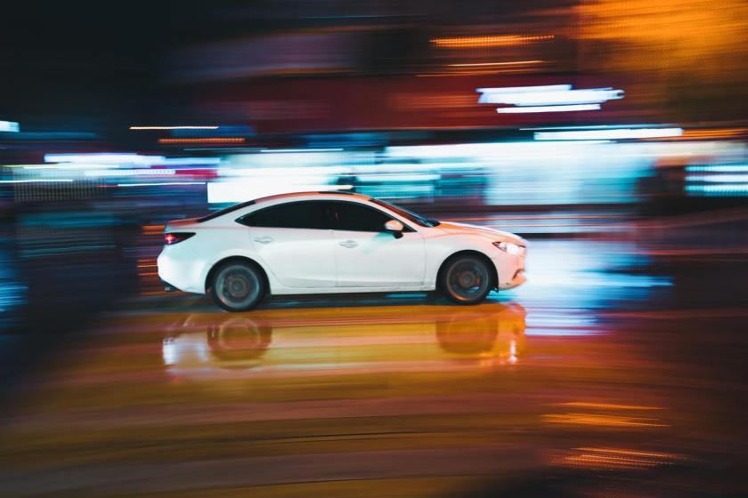 carro branco sedan andando a noite rapido