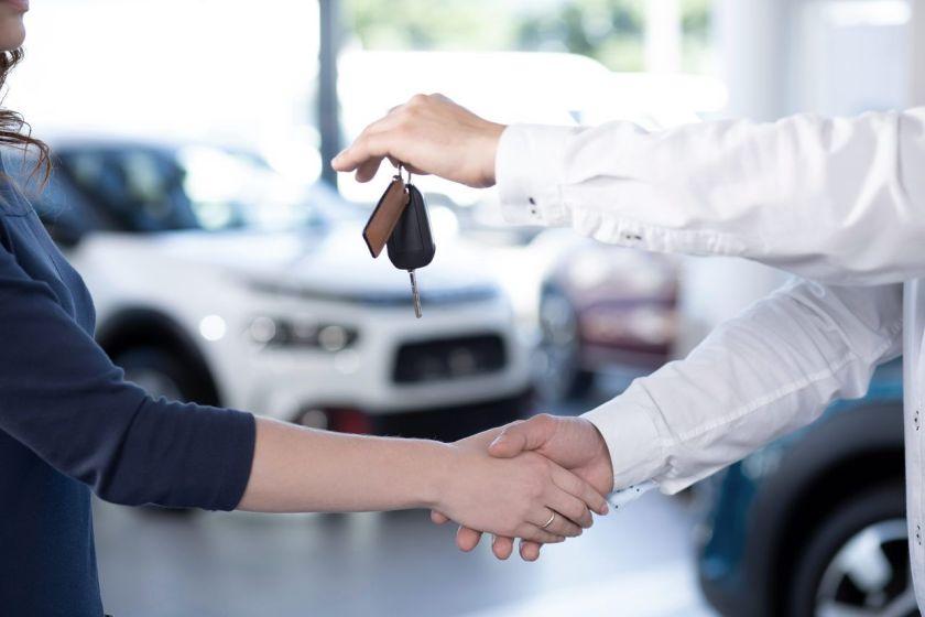 mulher aperta a mão de vendedor de carro após comprar seu veículo em concessionária