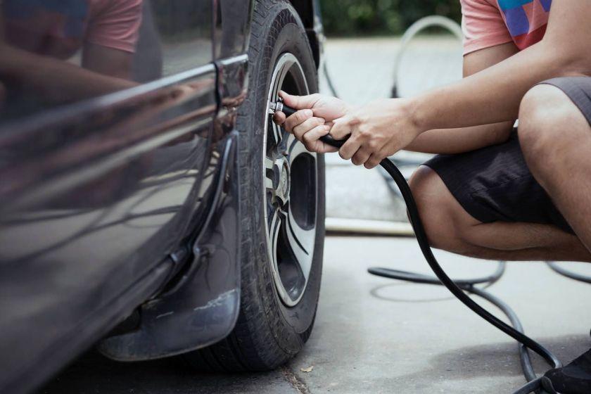 homem calibra pneus do carro