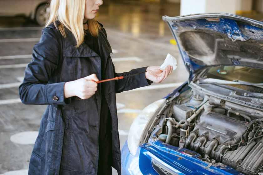 mulher checa o nível de óleo do motor do seu carro
