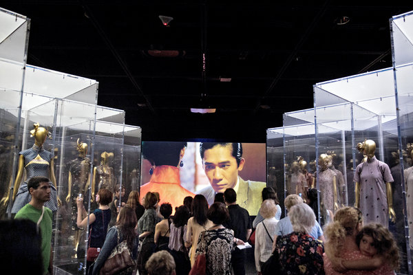 Visitors gathered to watch film clips in a room lined with clothing displays. Credit Damon Winter/The New York Times
