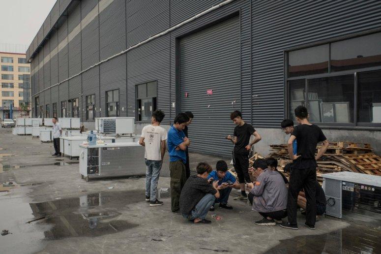工人们聚集在山东省某冰箱厂外。中国称能破坏臭氧层的某种气体的大肆排放并不普遍,但承诺予以打压。