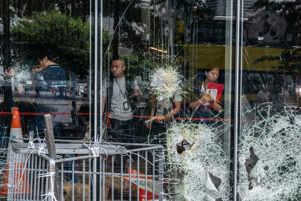 Scores of protesters damaged the facade of Hong Kong's Legislative Council hours before storming the building.