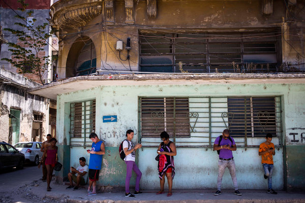 Smartphone users using their devices in Havana, Cuba, last year. On Monday, Cuba, put into effect new regulations that seek to expand internet access on the island.