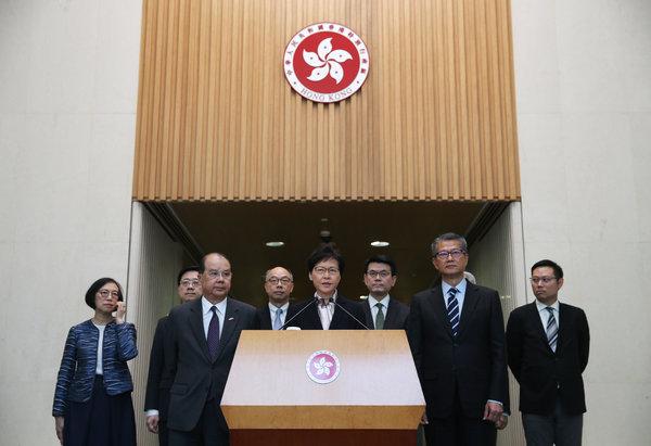 China ha dejado en gran medida que la jefa ejecutiva de Hong Kong, Carrie Lam (al centro), sofoque las protestas.