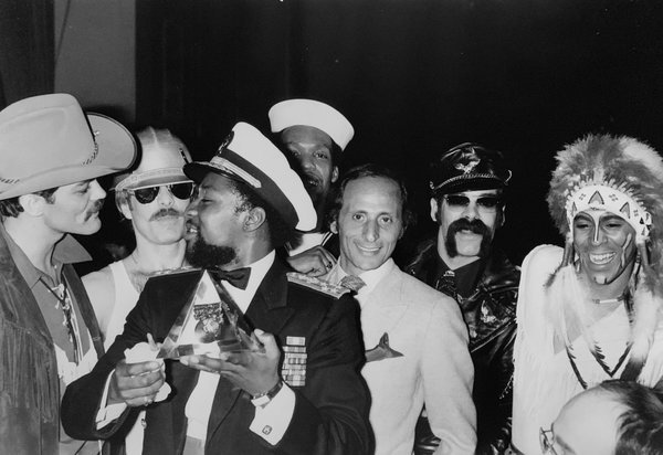 """Henri Belolo — he's the one without a costume — with the Village People in an undated photograph. Mr. Belolo and the composer Jacques Morali, a business partner, created the group in 1977 after, he recalled, they """"started to fantasize on what were the characters of America."""""""