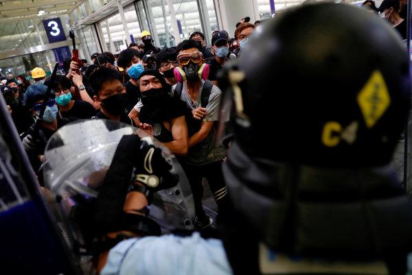 周二,在香港国际机场举行的大规模示威活动中,抗议者与防暴警察对峙。 Tyrone Siu/Reuters
