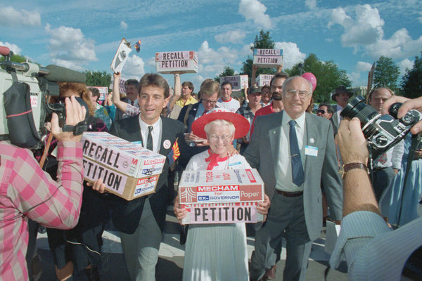 Mr. Buck, left, carrying boxes of petitions calling for the recall of Gov. Evan Mecham of Arizona in 1987. Mr. Buck originally championed Republican causes but later became a Democrat.