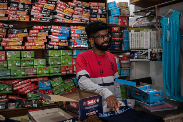 """Jeffrin Moses selling Tantex underwear and other clothing in the Khaderpet market in Tirupur, India's knitwear capital. Sales of underwear """"are down 50 percent,"""" he said."""