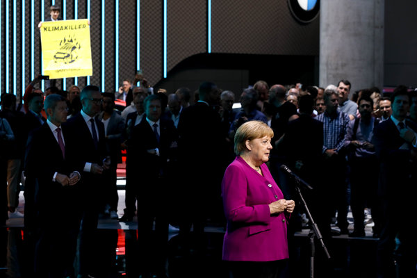 """A Greenpeace activist held up a placard reading, """"Climate Killer"""" as Chancellor Angela Merkel of Germany spoke at a car show in Frankfurt last week. Early in her tenure she was known as the """"climate chancellor."""""""