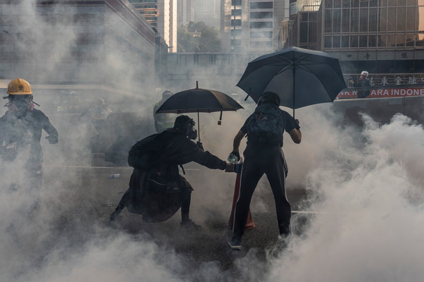 Protesters use a cone to control a tear gas canister in a standoff outside the Legco Building in Hong Kong on Tuesday.
