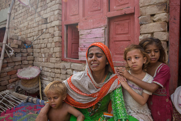Ghazala Bibi, center, with her three remaining children.Her 9-year-old son, Ali Husnain is believed to have been killed by the same person who killed Muhammad Faizan.