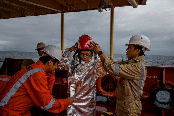 Arnulfo Abad, center, the engine-room fitter, being helped into fireproof clothing during a safety drill.