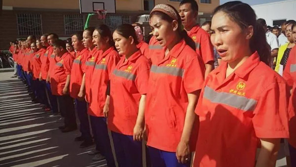 Workers in uniform at a labor compound in eastern Xinjiang, China, in 2017.