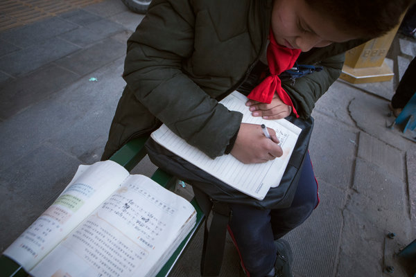 A Uighur child doing his Chinese homework at a bus stop.The government says minority children will have better prospects if they are fluent in Chinese, but Uighur activists worry about losing their culture.