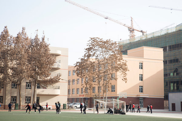 Students in Hotan playing soccer in a schoolyard with a dormitory in the background.