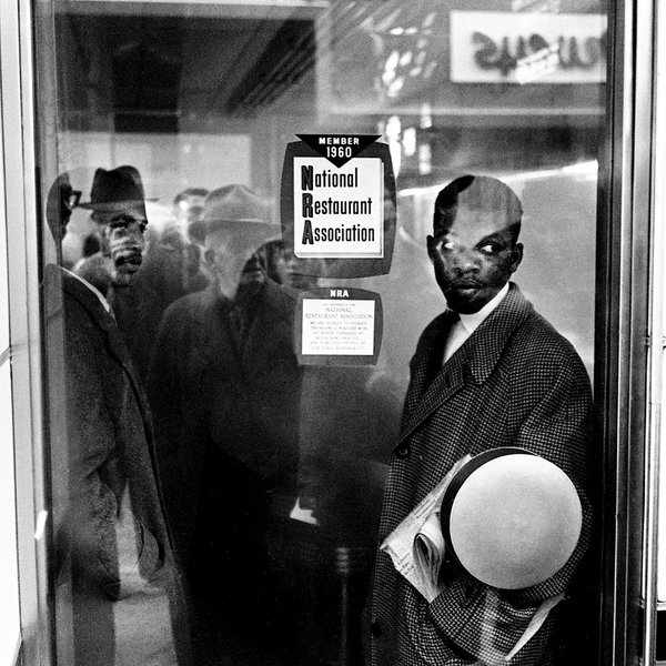Mr. Lewis, right, and a fellow student demonstrator, James Bevel, stood inside the door of a Nashville restaurant in 1960 during a sit-in to protest the establishment's refusal to serve Black people.