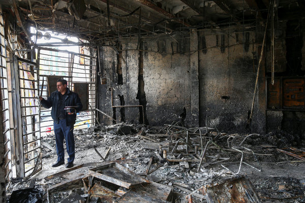 A man inspects the ruins of a Tehran bank in November after Iranians protested a surprise increase in gasoline prices.