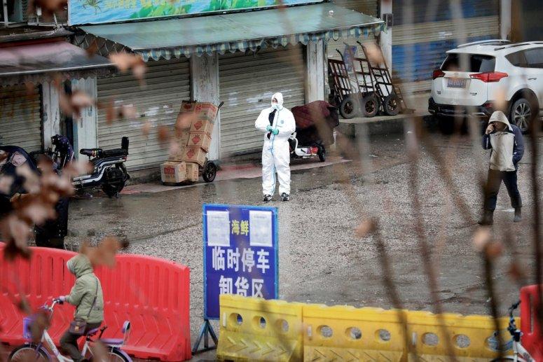 周一,穿着防护服的工作人员在武汉一个已经封闭的海鲜市场。