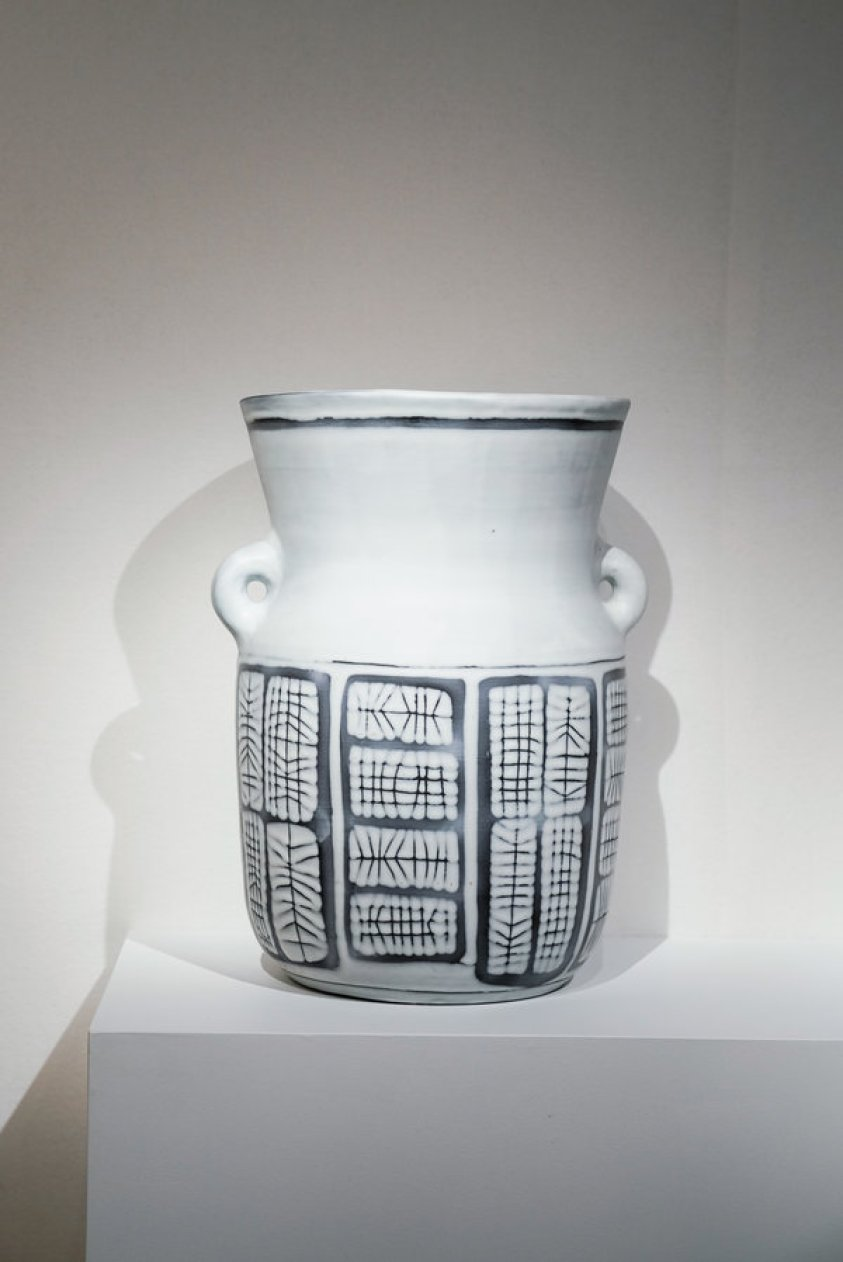 white ceramic vase with black and grey patterning and two handles on the sides