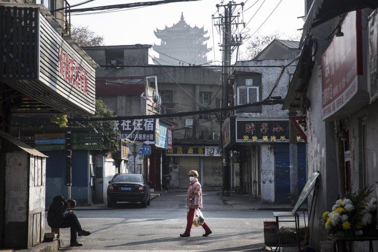 周五,一名居民购物归来,走在武汉几乎空无一人的街道上。