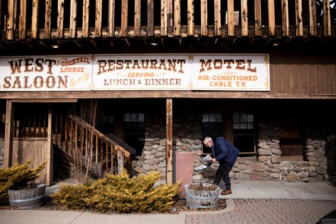 Mr. Butz putting copies of The Messenger in a distribution box outside the Golden West Saloon in Loyalton, Calif.