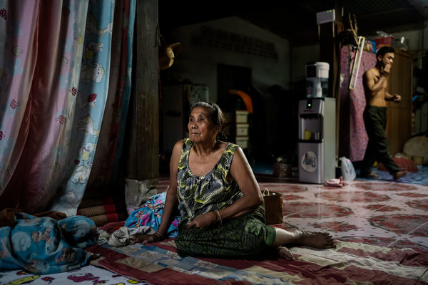 Amkha Janlong watches TV as her son-in-law, Wittaya Thongnet, walks behind her in the home they live in by the Mekong River.