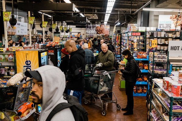 People lining up at registers at Fairway in Harlem on Friday.Some stores were overwhelmed with lines of customers waiting to enter.