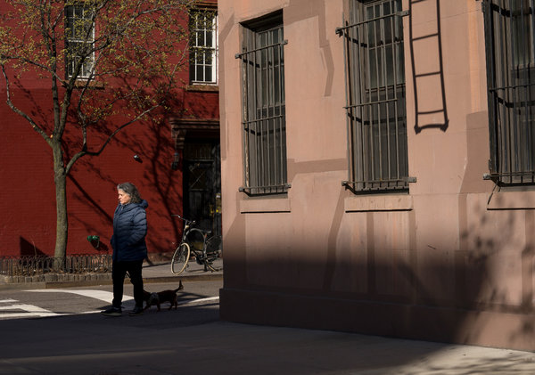 Fresh air? A lone New Yorker waits to cross an uncrowded street.