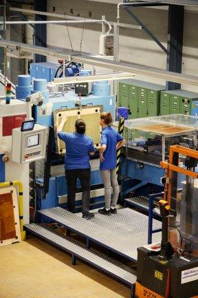 Empleadas de Ravensburger inspeccionan una herramienta cortadora que convierte una imagen sólida de cartón en un rompecabezas.