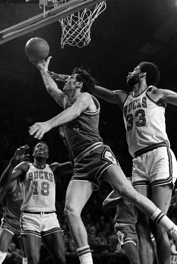 Sloan slipped past Kareem Abdul Jabbar, right, to score two points in a game against the Milwaukee Bucks in 1974. No. 18 for the Bucks was Curtis Perry.