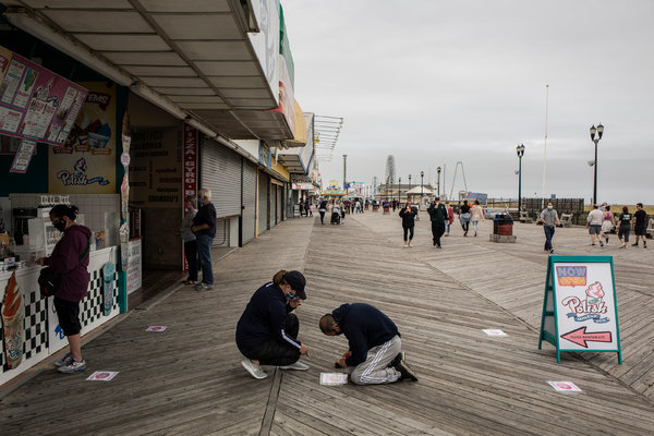 "Placing social distancing markers at a boardwalk business in Seaside Heights, N.J., on Friday. In neighboring New York, Gov. Andrew M. Cuomo said gatherings of up to 10 people would be allowed ""for any lawful purpose."""