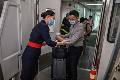 A flight attendant checks the body temperature of a passenger at the door of a plane at the Tianhe Airport in Wuhan on Friday.