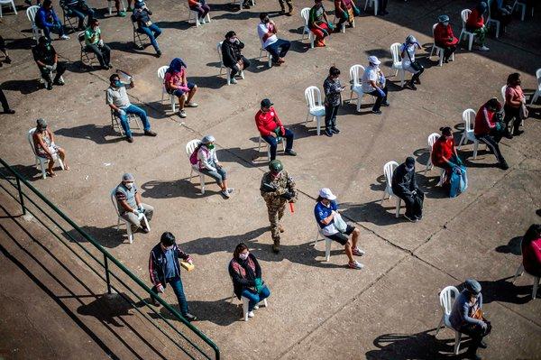 Trabajadores de un mercado en Lima esperan la prueba de coronavirus que administra el Ministerio de Salud.