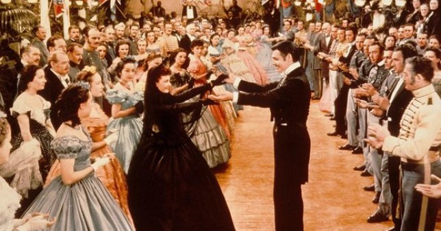 The film's producers hired two white technical advisers to ensure accurate depiction of Southern accents and manners, like whether Scarlett O'Hara (here, dancing with Rhett Butler), would wear a hat at an evening party, but disregarded many concerns raised by African-American leaders.