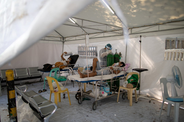 A health worker replaced an oxygen tank in a tent set up in a hospital parking lot for coronavirus patients in Manila in April.